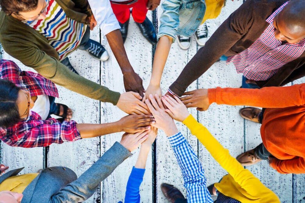 Blick auf Menschen, die im Kreis stehen und ihre Hände in der Mitte feierlich aufeinanderlegen