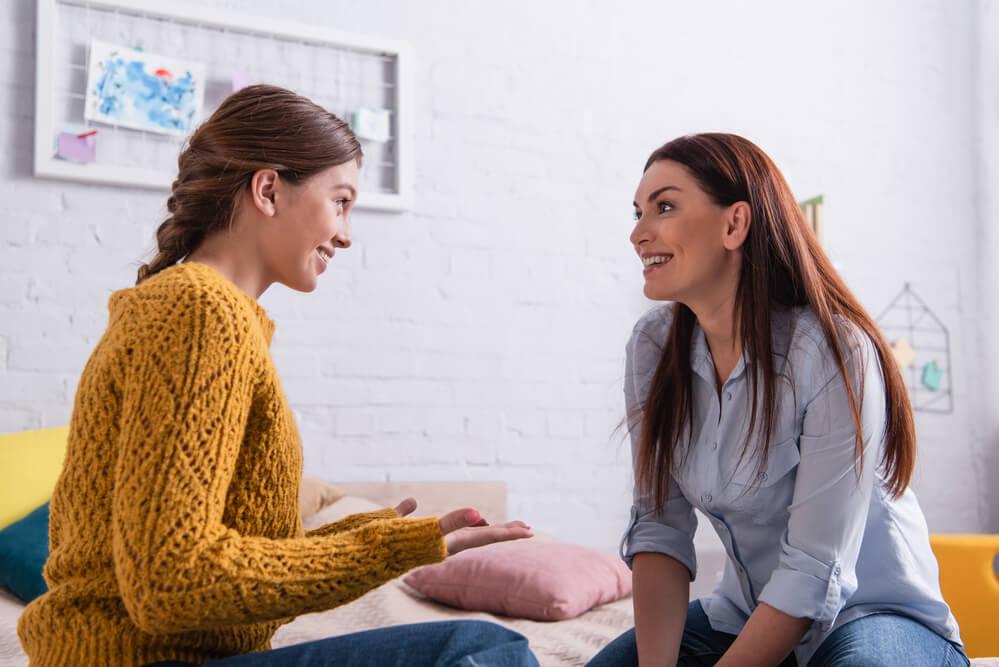 Mutter hört jugendlicher Tochter zu und beide freuen sich im Gespräch miteinander.