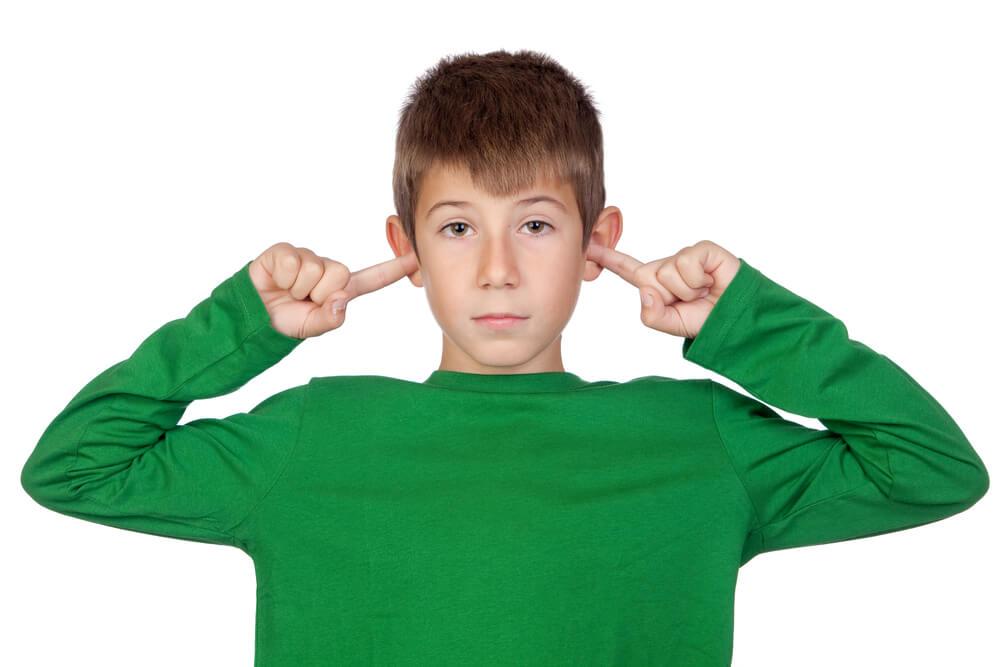 Junge schaut genervt und hat die Finger in den Ohren