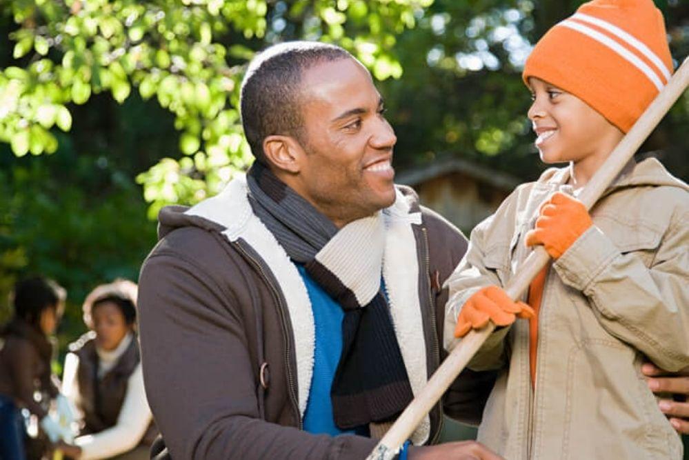 Gleichwertigkeit in der Beziehung zum Kind: Vater und Sohn auf Augenhöhe im Garten