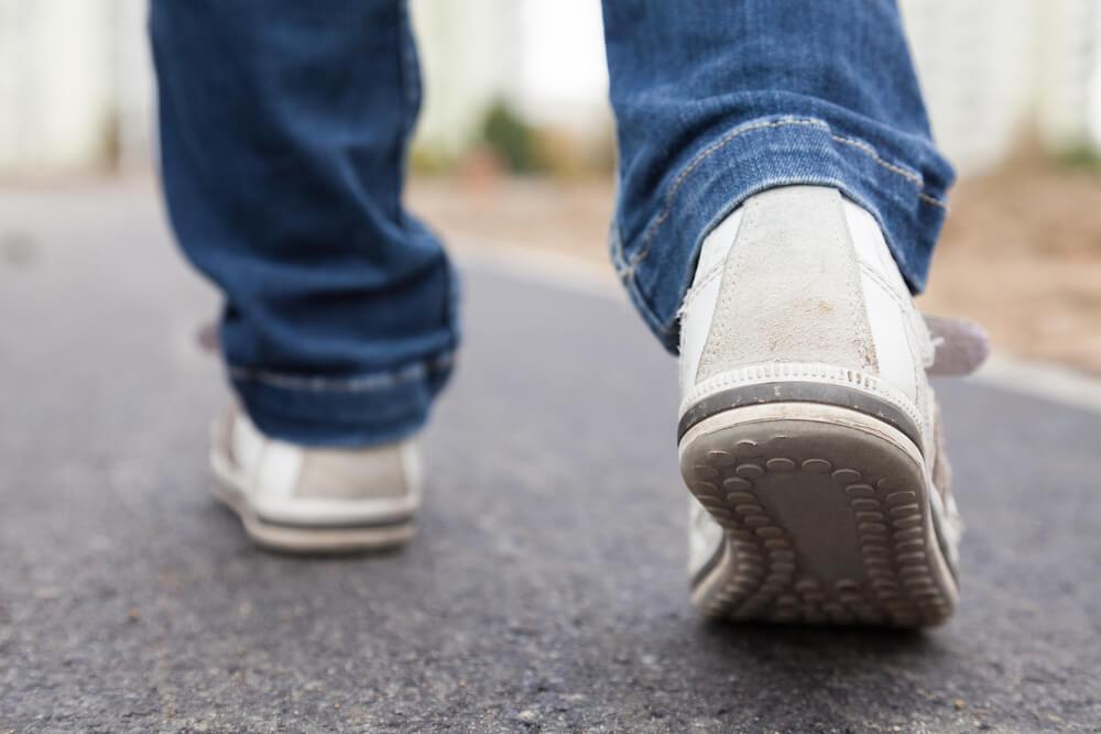 Schuhe und Jeans von einem Jugendlichen laufen auf der Straße weg.