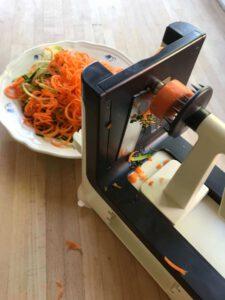 Gemüsespiralschneider in schwarz-weiß mit einem bunten Teller von Karotten und Zucchini-Spaghetti.