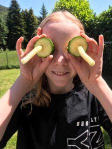 Mädchen steht im sonnigen Garten mit Zucchini-Resten vom Gemüsespiralschneider als lustige Augen.